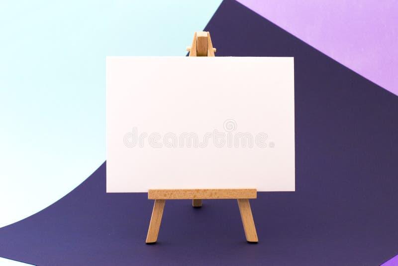 Livre blanc sur peu de chevalet sur le fond coloré photographie stock