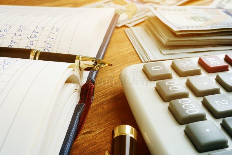 Livre, calculatrice et argent de comptes Budget mensuel à la maison images libres de droits