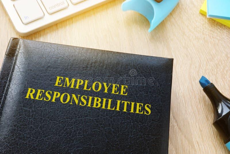 Livre concernant des responsabilités des employés sur une table images libres de droits