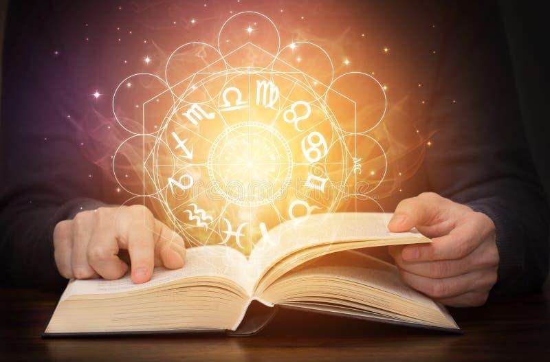 Livre d'astrologie avec les signes de zodiaque et la lumière brillante image stock