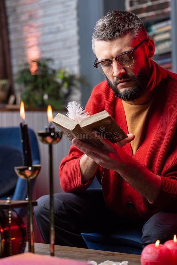 Livre d'astrologie de lecture de diseur de bonne aventure se reposant à la table avec des bougies image libre de droits