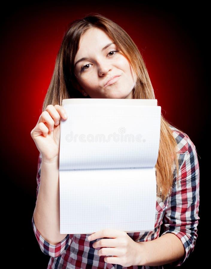 Jeune fille déçue tenant le livre d'exercice images stock