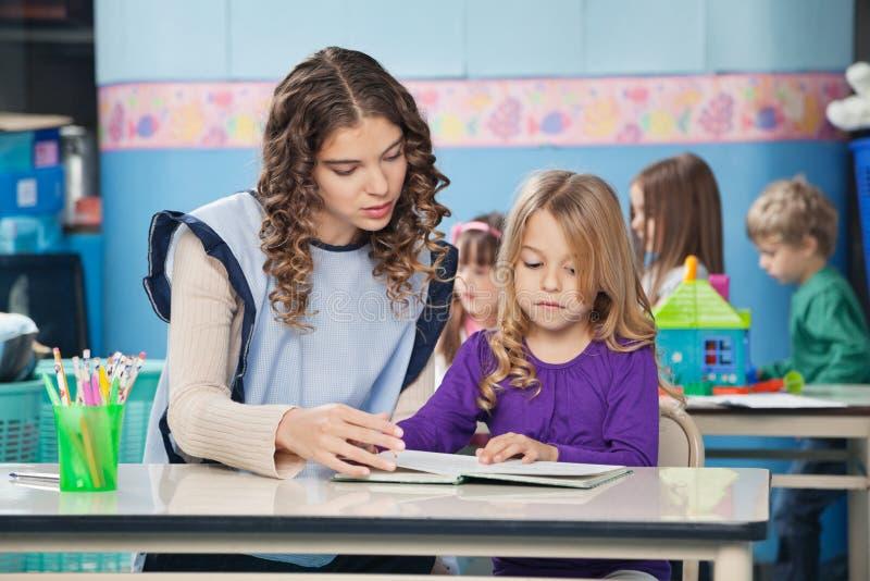 Livre d'And Girl Reading de professeur avec des enfants dedans photo libre de droits