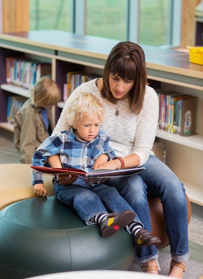 Livre d'And Schoolboy Reading de professeur dans la bibliothèque photographie stock libre de droits