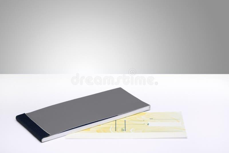 Livre de chèque et un chèque en blanc photographie stock libre de droits