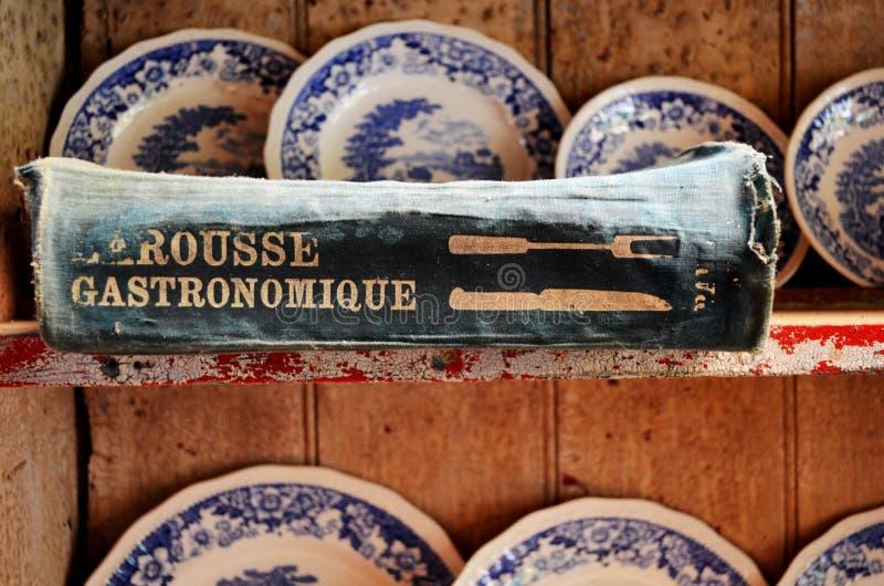 Livre de cuisine de Larousse Gastronomique sur une vieille raboteuse française images stock
