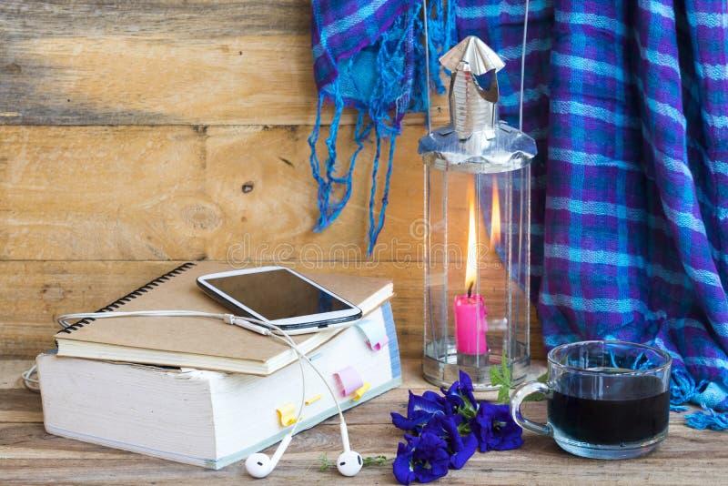 Livre de dictionnaire, téléphone mobile pour étudier avec des boissons à base de plantes, foulard bleu, lampadaire en hiver photos libres de droits