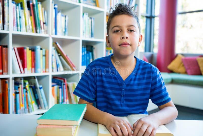 Livre de lecture élémentaire de garçon dans la bibliothèque d'école photographie stock