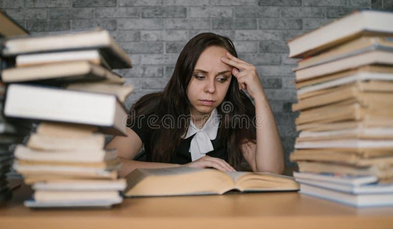 Livre de lecture étant ennuyeux d'étudiante à la bibliothèque avec beaucoup de livres à l'université Livre de lecture découragé p images stock