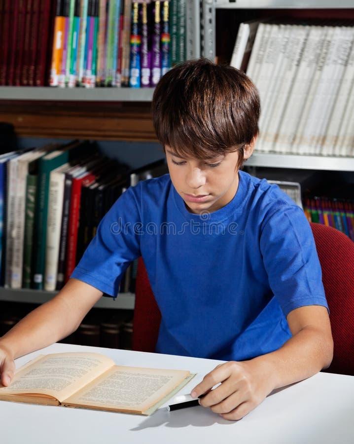 Livre de lecture adolescent d'écolier dans la bibliothèque image stock