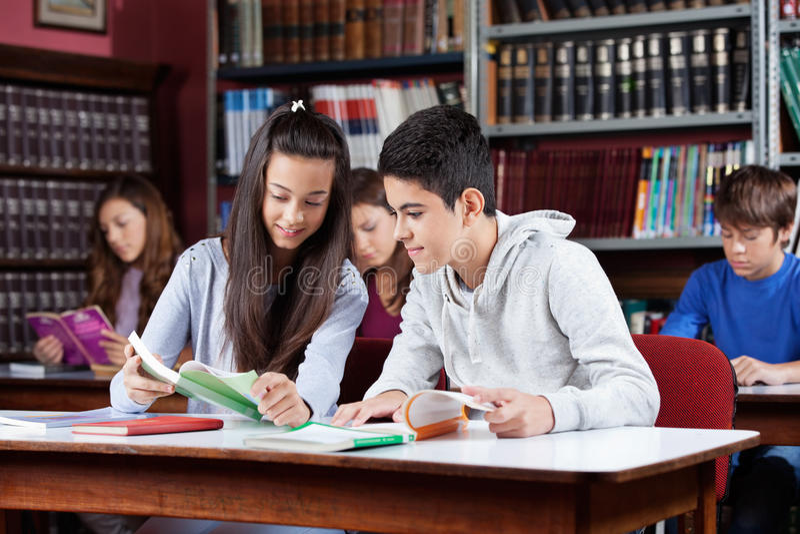 Livre de lecture adolescent de camarades de classe dans la bibliothèque photo libre de droits