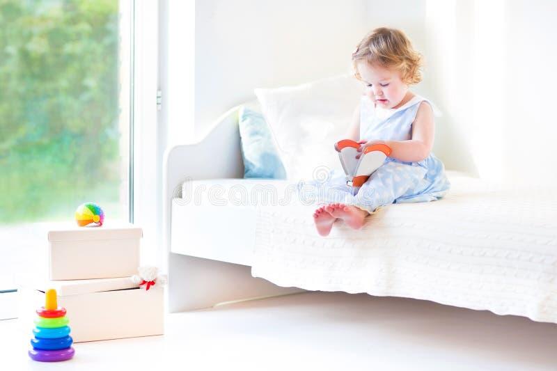 Livre de lecture adorable de fille d'enfant en bas âge se reposant sur le lit blanc photographie stock