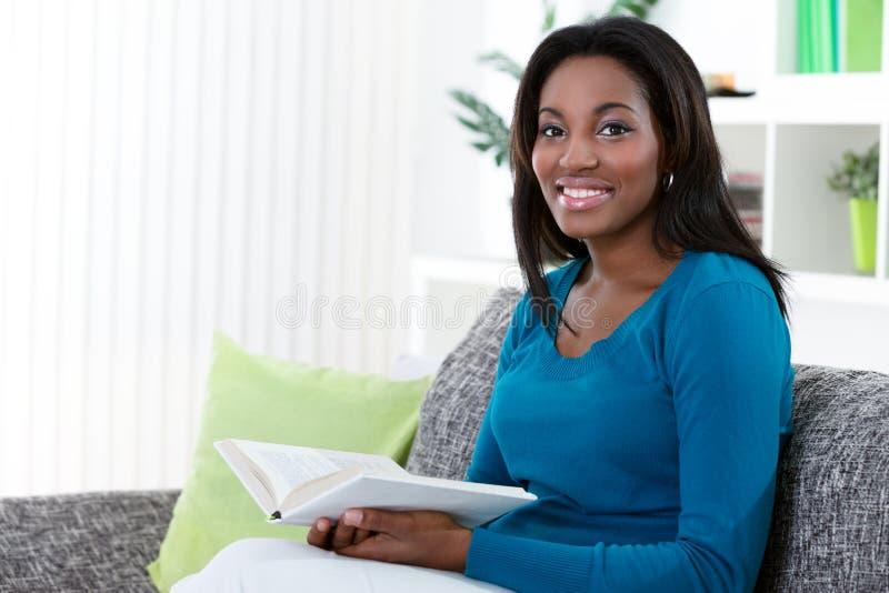 Livre de lecture africain de femme photos stock