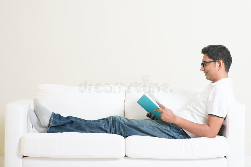 Livre de lecture asiatique d'homme sur le divan photos stock