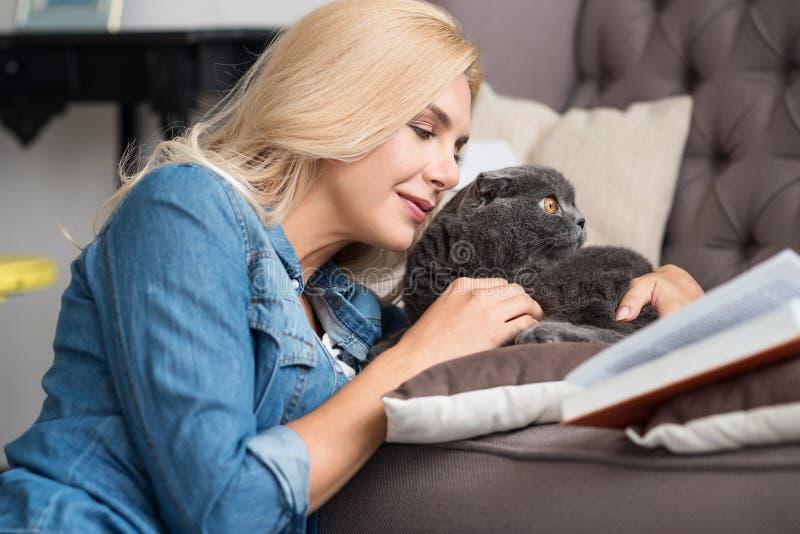 Livre de lecture assez blond de femme avec son chat photo libre de droits
