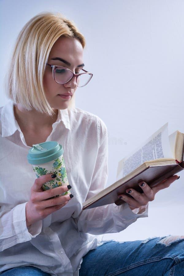 Livre de lecture attrayant d'étudiante et tenir la rétro tasse de café à disposition image stock