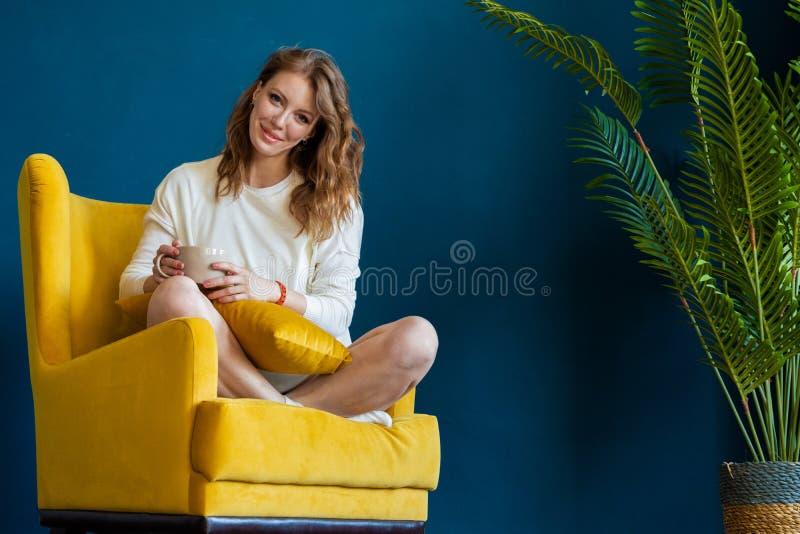 Livre de lecture blond de femme à la maison, buvant du café ou du thé et se reposant dans le fauteuil photos libres de droits