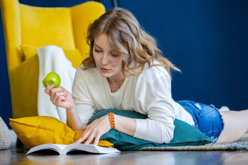 Livre de lecture blond de femme à la maison et s'étendant sur le plancher à côté du fauteuil jaune photographie stock