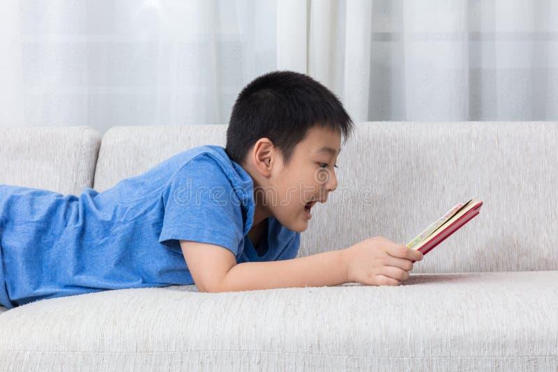 Livre de lecture chinois asiatique de petit garçon sur le sofa photographie stock libre de droits
