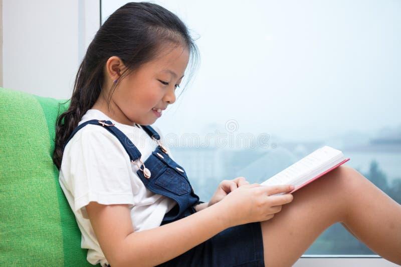 Livre de lecture chinois asiatique de petite fille sur le rebord de fenêtre images libres de droits