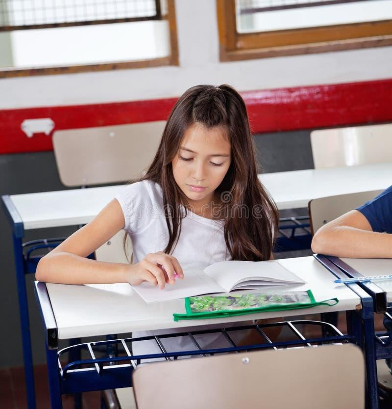 Livre de lecture d'écolière au bureau dans la salle de classe photos libres de droits