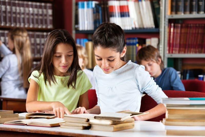Livre de lecture d'écolières ensemble au Tableau dedans photo libre de droits