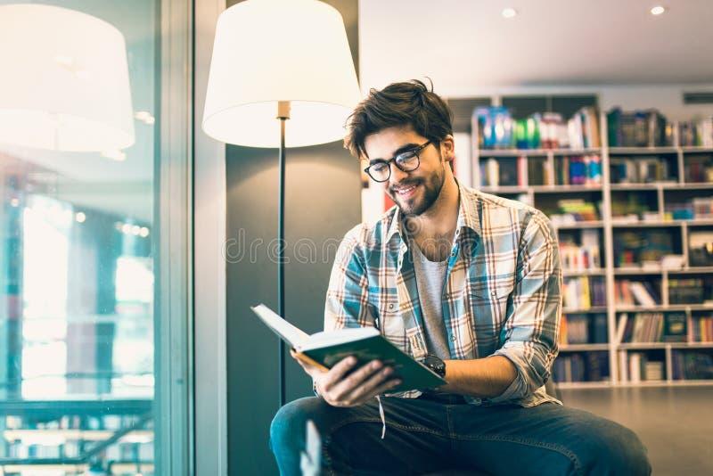 Livre de lecture d'homme dans la bibliothèque image stock