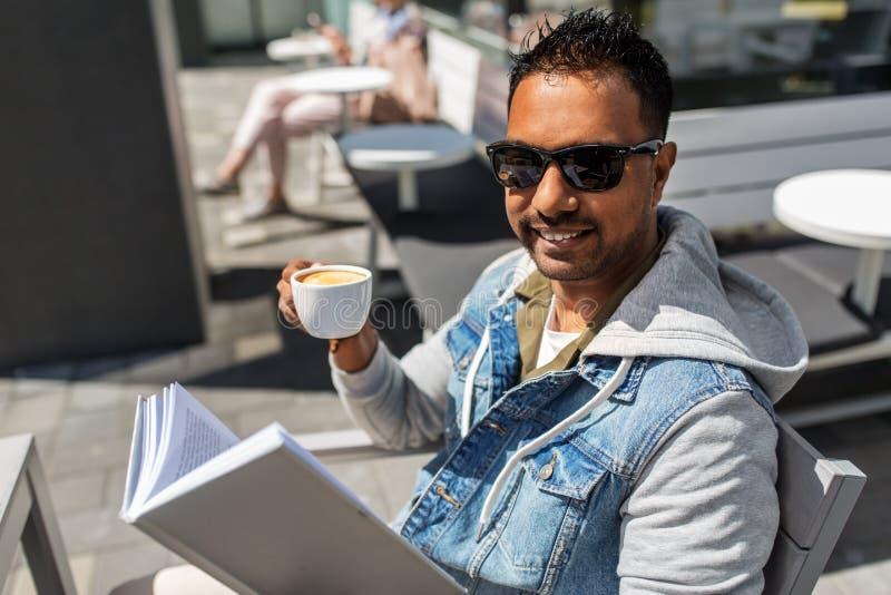 Livre de lecture d'homme et café potable au café de ville photo libre de droits