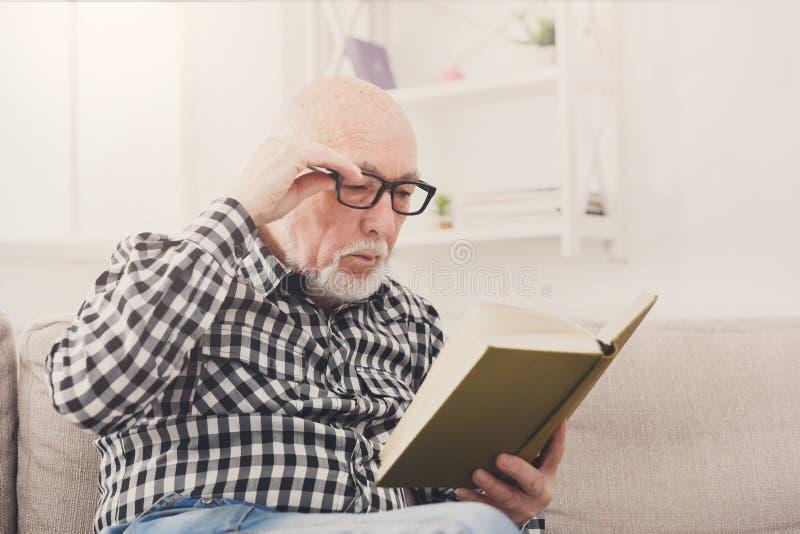 Livre de lecture d'homme supérieur à la maison, l'espace de copie images stock