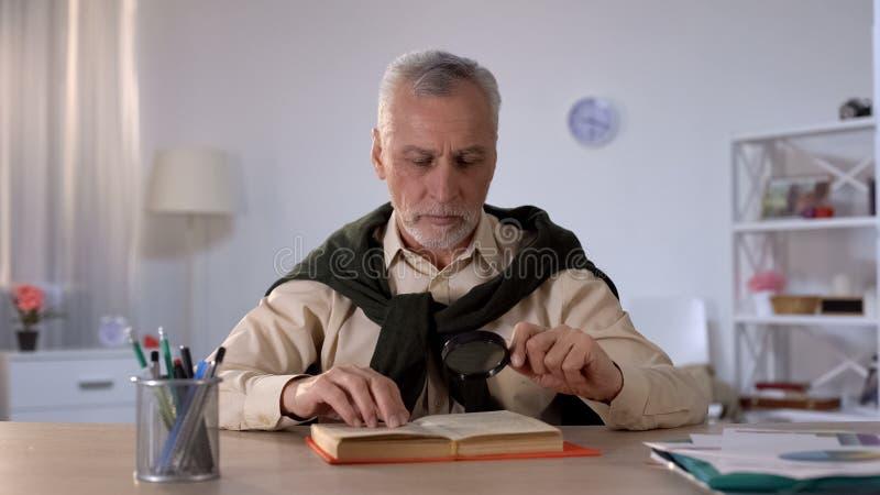 Livre de lecture d'homme supérieur avec la loupe, attention aux détails, érudition photos libres de droits