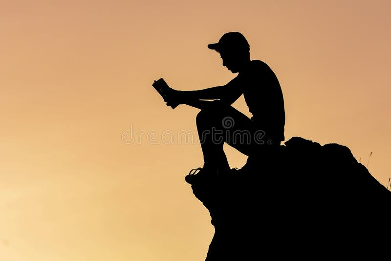 Livre de lecture d'homme sur la roche photos stock