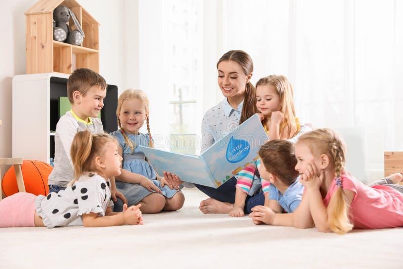 Livre de lecture d'institutrice gardienne aux enfants ?tude et jouer image libre de droits