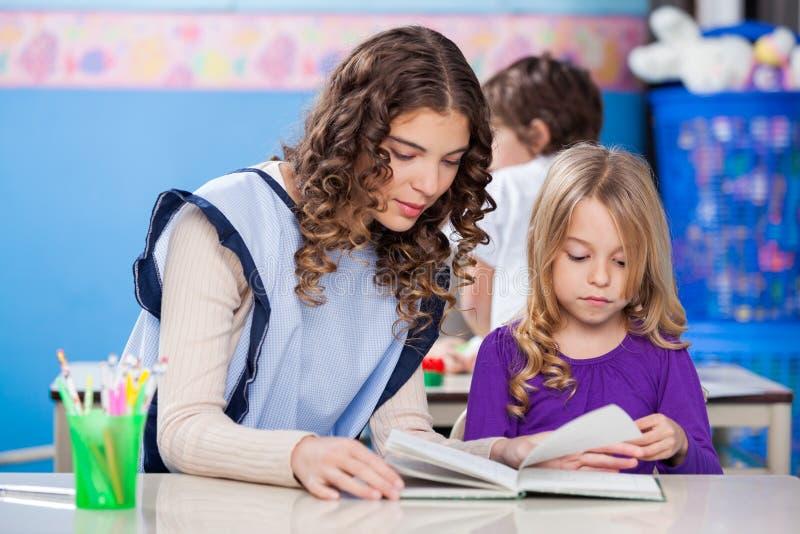 Livre de lecture d'And Little Girl de professeur dans la salle de classe images libres de droits