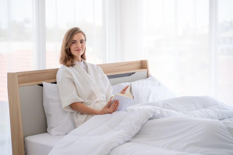 Livre de lecture dans le lit Livre de lecture de personne féminine dans le lit pendant le matin photo stock