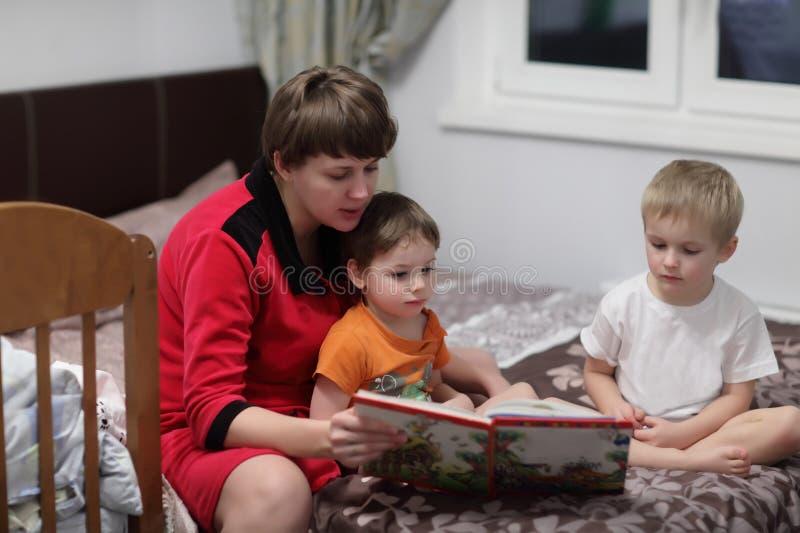 Livre de lecture de famille photos stock