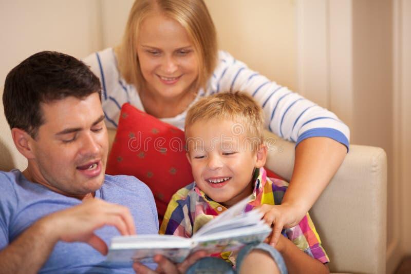 Livre de lecture de famille ensemble à la maison photo stock