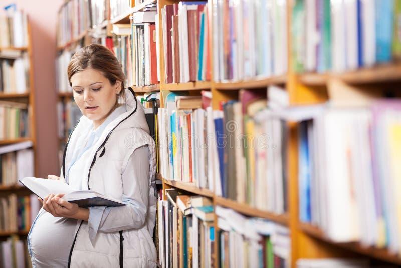 Livre de lecture de femme enceinte de jeunes photo stock