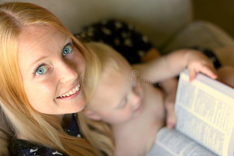 Livre de lecture de femme tandis que tout en tenant le bébé images libres de droits