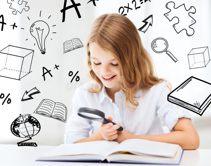 Livre de lecture de fille avec la loupe à l'école photos libres de droits