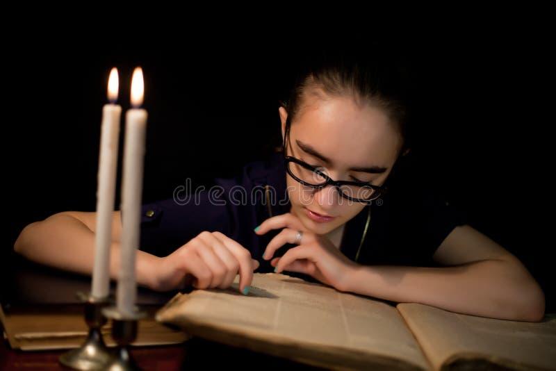 Livre de lecture de fille dans la bibliothèque foncée images stock