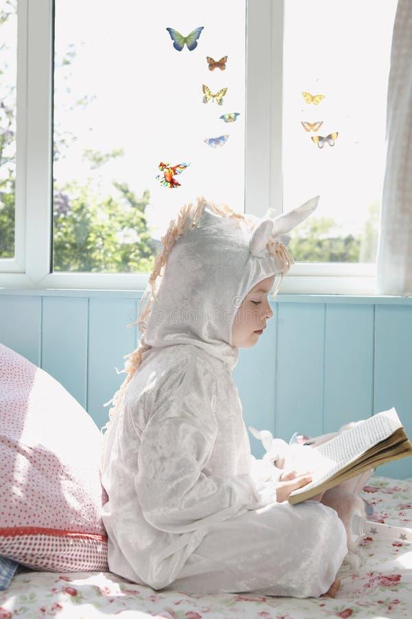 Livre de lecture de fille en Unicorn Costume On Bed image libre de droits