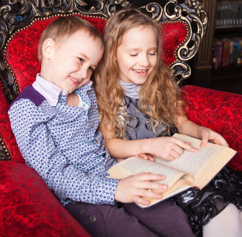 Livre de lecture de garçon et de fille à la maison images libres de droits