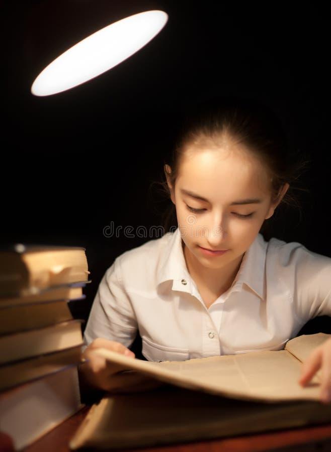 Livre de lecture de jeune fille à l'obscurité de nuit à la bibliothèque image libre de droits