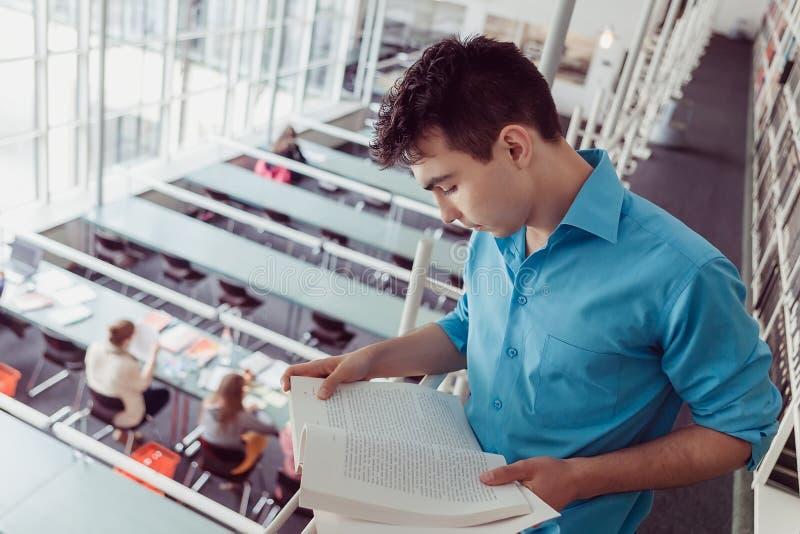 Livre de lecture de jeune homme dans la bibliothèque photos libres de droits