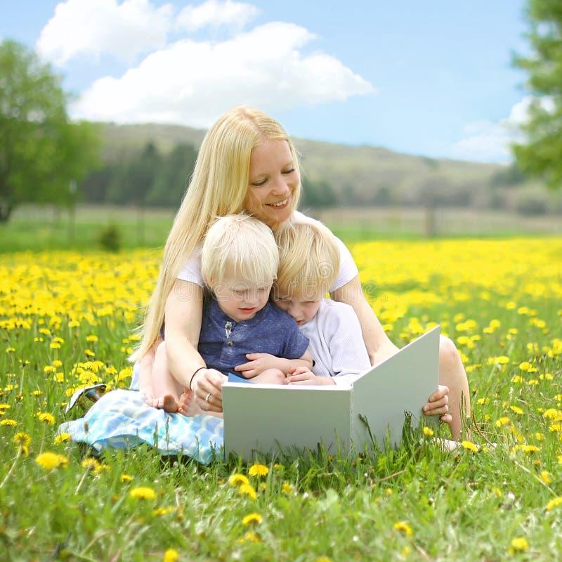 Livre de lecture de mère aux enfants en bas âge dehors images libres de droits