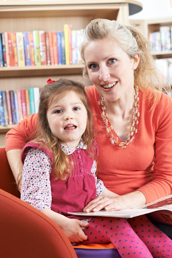 Livre de lecture de mère et de fille dans la bibliothèque photographie stock
