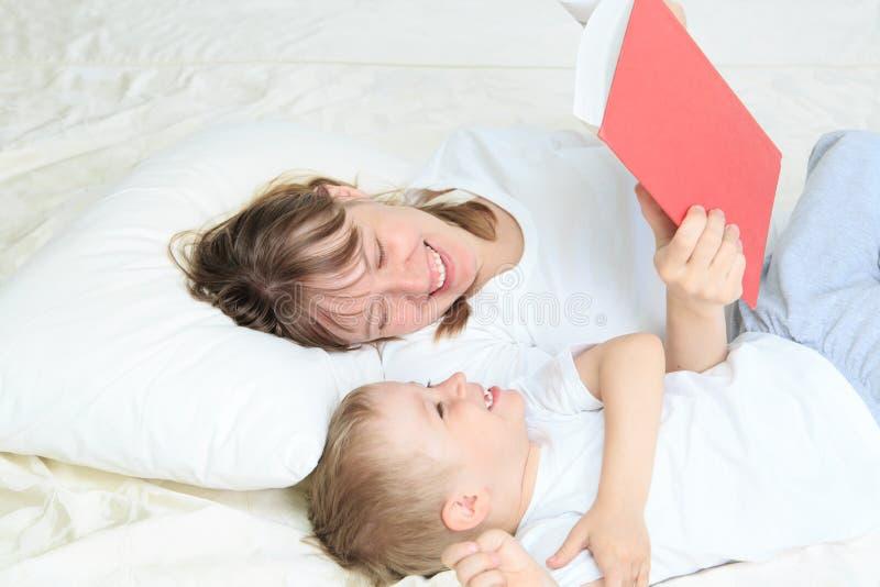 Livre de lecture de mère et de fils dans le lit photos stock