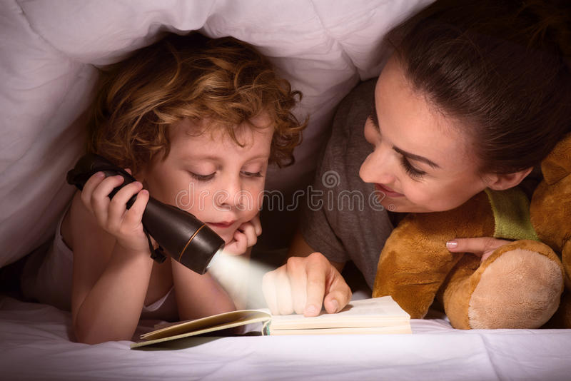 Livre de lecture de mère et de fils sous la couverture photos stock