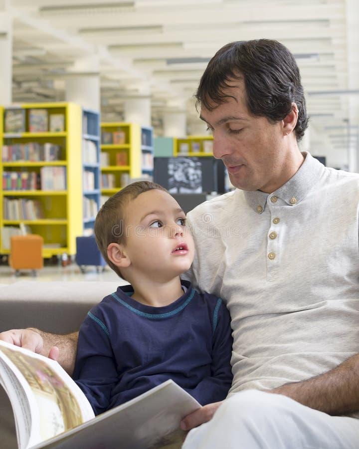 Livre de lecture de père et d'enfant photo stock