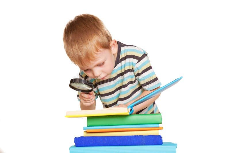 Livre de lecture de petit garçon avec la loupe image stock